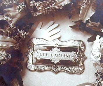 Coffin plate photographed with wreath. See below for full image.